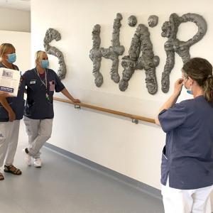 Personal står framför en vägg och tittar på ett konstverk i form av bokstäver.