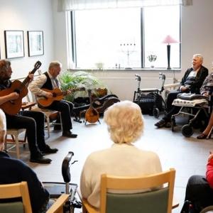 Två gitarrister underhåller människor på ett demensboende