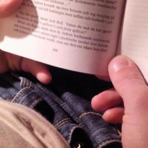 En hand håller i en uppslagen bok