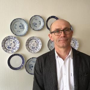 Max Liljefors är konstvetare från Lunds universitet och sa forska på effekterna av konstvandringen på Nacka sjukhus. Syntolkning; porträttbild av Max framför porslin från Gustavsberg.